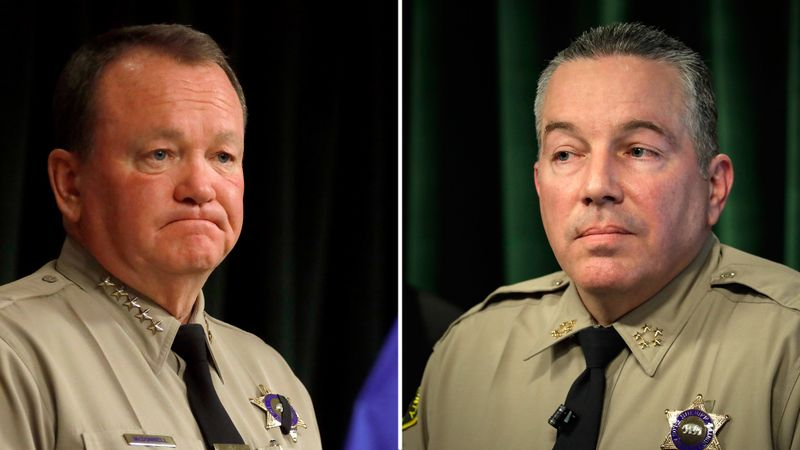 In July 2018, then-Sheriff Jim McDonnell, left, launched a study of cliques with matching tattoos. Current Sheriff Alex Villaneuva has downplayed the significance of deputies with matching tattoos. The two men are seen in undated file photos. (Credit: Los Angeles Times)