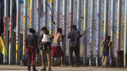 At center, a 22-year-old Honduran man says final words to his wife before he squeezed through the pillars in Tijuana on Wednesday carrying his young child. (Thomas E. Franklin/Los Angeles Times)