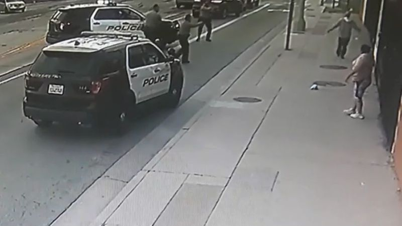 South Gate police officers point their guns at Daniel Canizales, upper right, moments before he was shot on Paramount Boulevard on Jan. 29 in an image from video released by his attorney, Luis Carillo.