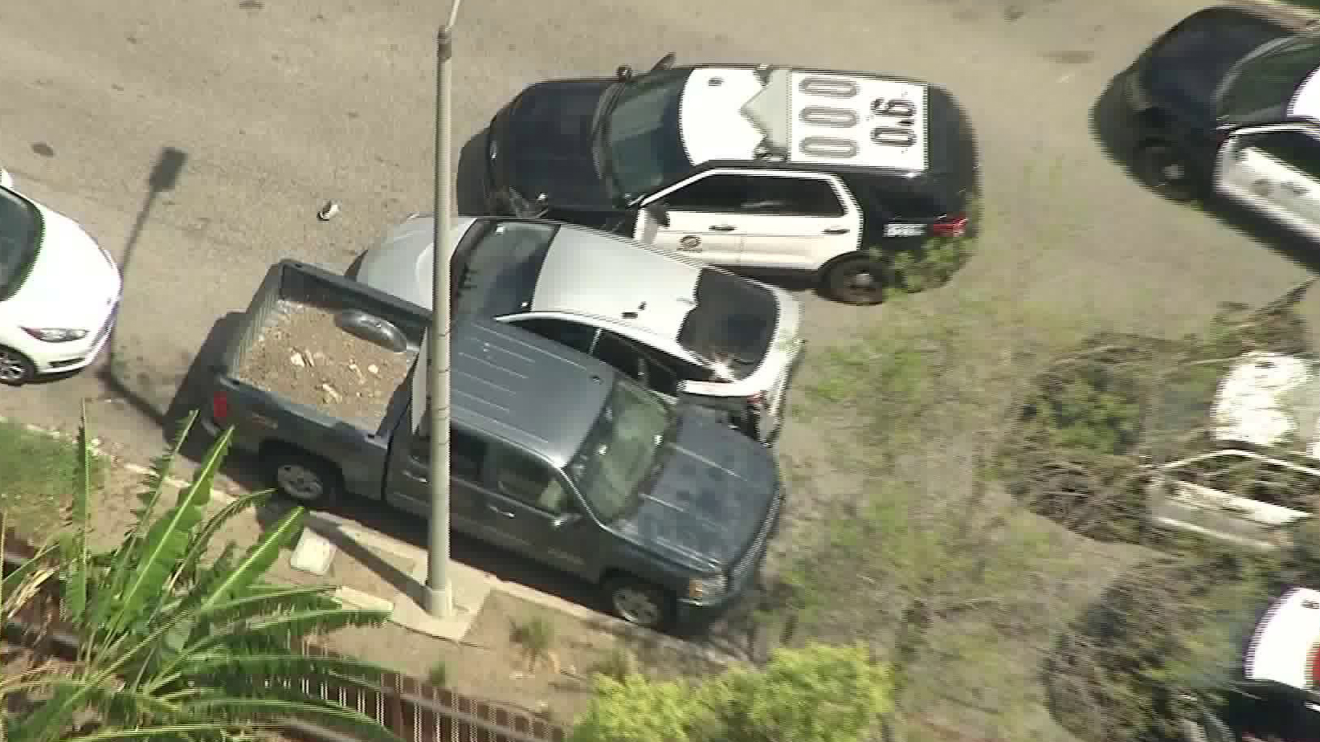 A Prius is seen wedged between an LAPD patrol vehicle and a parked truck in East Hollywood on April 4, 2019, bringing an end to a police chase. (Credit: KTLA)