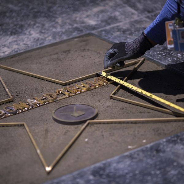 Workers replace the star of President Donald J. Trump on the Hollywood Walk of Fame after it was destroyed by a vandal in the early morning hours on July 25, 2018 in Los Angeles. (Credit: DAVID MCNEW/AFP/Getty Images)