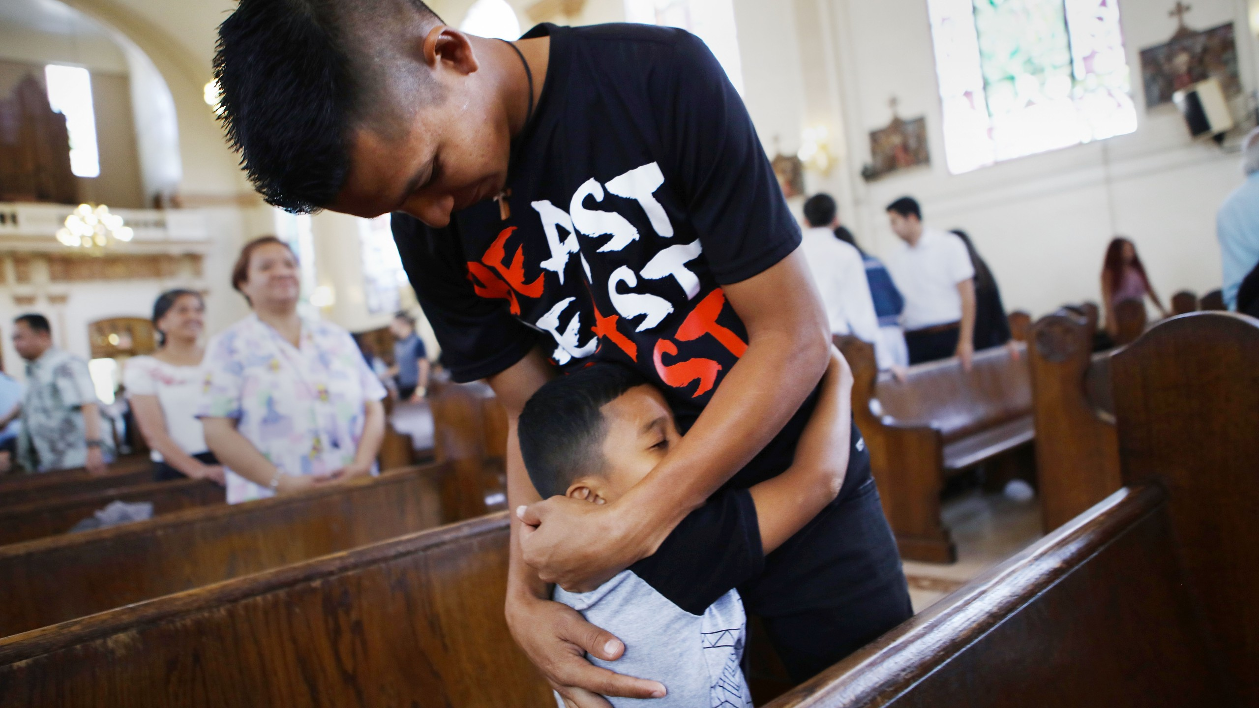 Honduran father Juan and his 6-year-old son, Anthony, asylum seekers who were separated for 85 days after crossing into the U.S. at a lawful port of entry in Texas, embrace while attending Sunday mass in Oakland on Sept. 9, 2018. (Credit: Mario Tama / Getty Images)