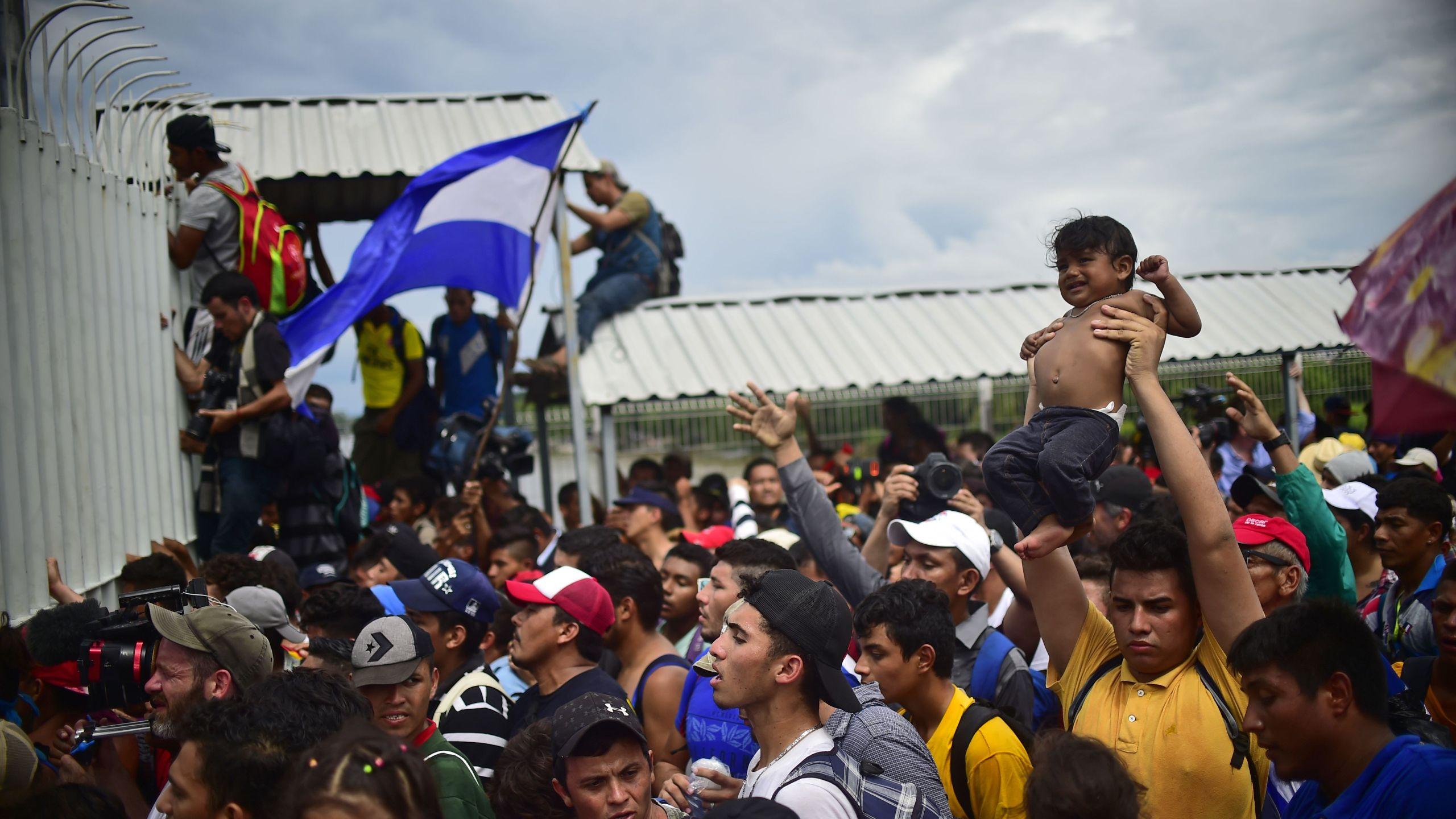 Honduran migrants heading in a caravan to the U.S. climb the gate of the Guatemala-Mexico international border bridge in Ciudad Hidalgo, Chiapas state, Mexico, on Oct. 19, 2018. (Credit: PEDRO PARDO/AFP/Getty Images)