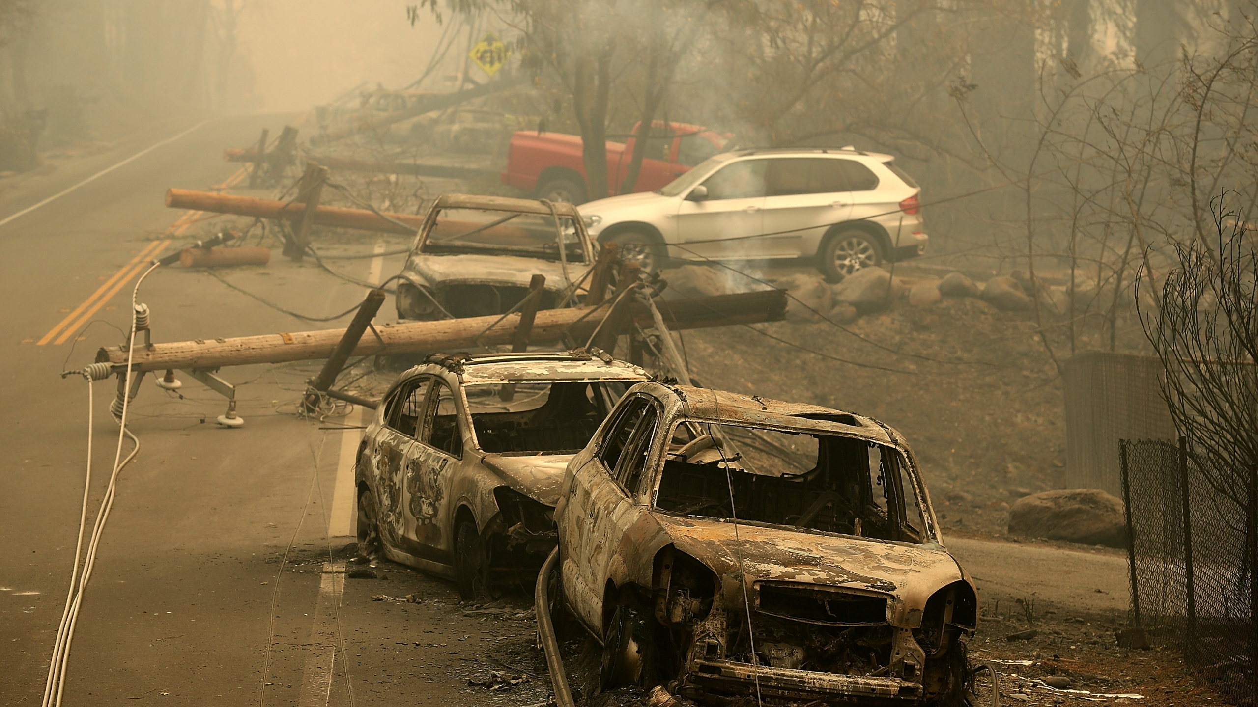 Power lines rest on cars that were burned by the Camp Fire on Nov. 10, 2018, in Paradise, Calif. (Credit: Justin Sullivan/Getty Images)