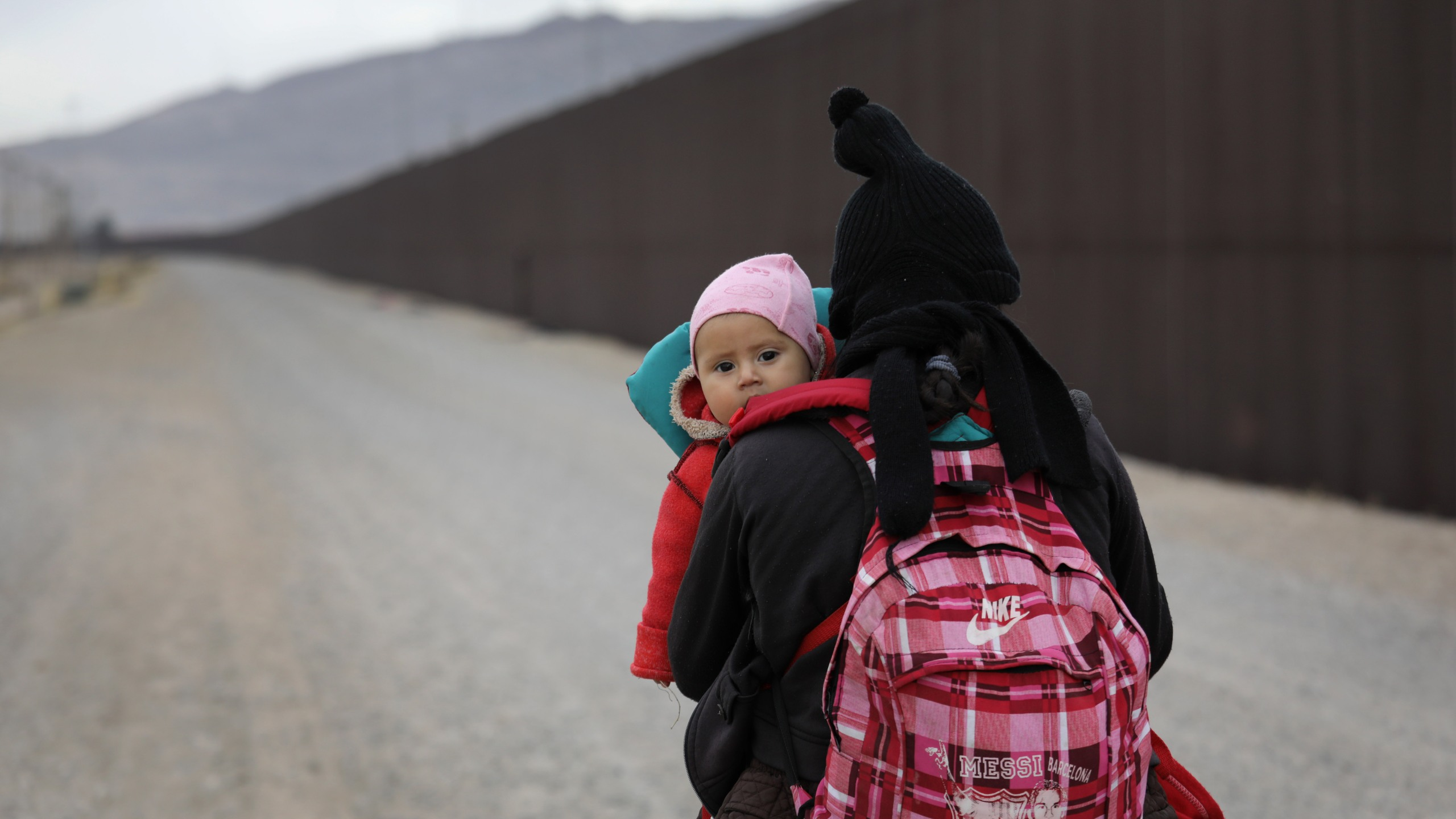 Central American migrants walk along the border fence after crossing the Rio Grande from Mexico on Feb. 1, 2019 in El Paso, Texas. (Credit: John Moore/Getty Images)