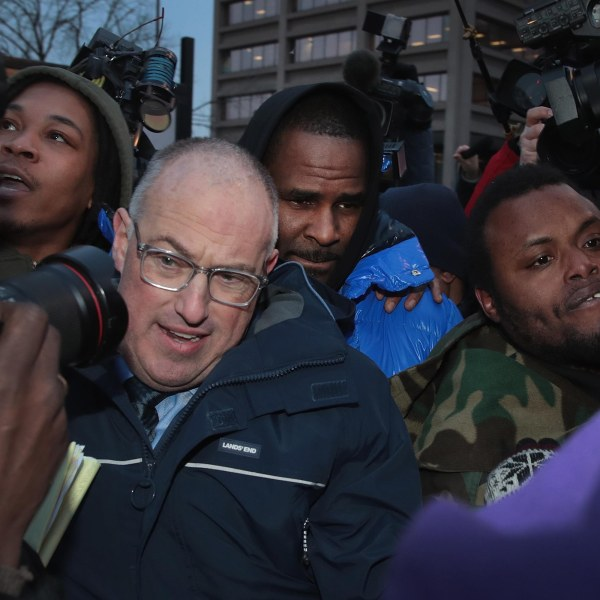 R&B singer R. Kelly and his attorney Steve Greenberg fight their way through photographers outside of the Cook County jail after posting bond on Feb. 25, 2019 in Chicago. (Credit: Scott Olson/Getty Images)