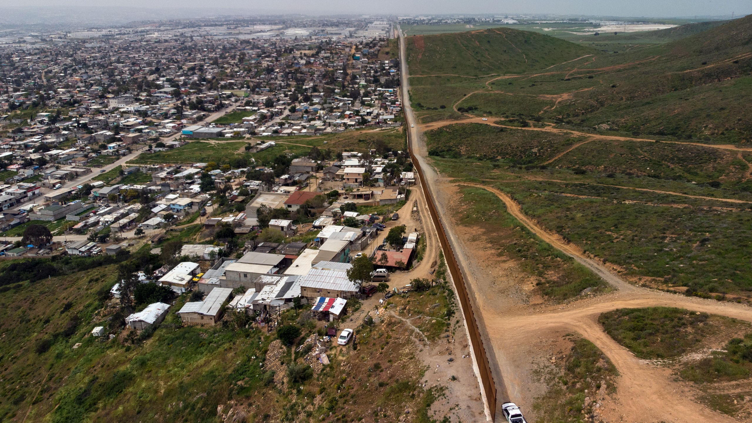 In this aerial view, a Border Patrol unit is positioned next to a section of the U.S.-Mexico border fence as it ends — Mexico on the left side and the U.S. on the right — at El Nido de las Aguilas in eastern Tijuana on March 26, 2019. (Credit: Guillermo Arias / AFP / Getty Images)