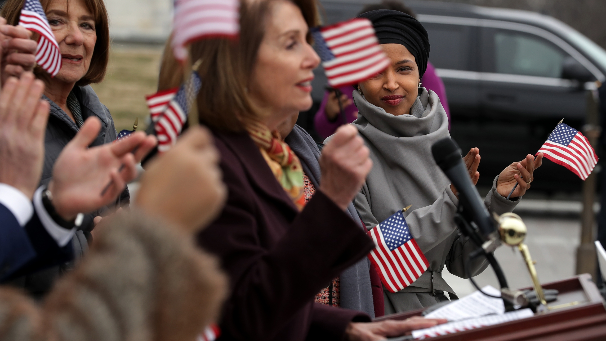 Rep. Ilhan Omar (D-MN) (R) listens to Speaker of the House Nancy Pelosi (D-CA) during a rally for H.R. 1, or the We The People Act, on the East Steps of the U.S. Capitol March 8, 2019. (Credit: Chip Somodevilla/Getty Images)