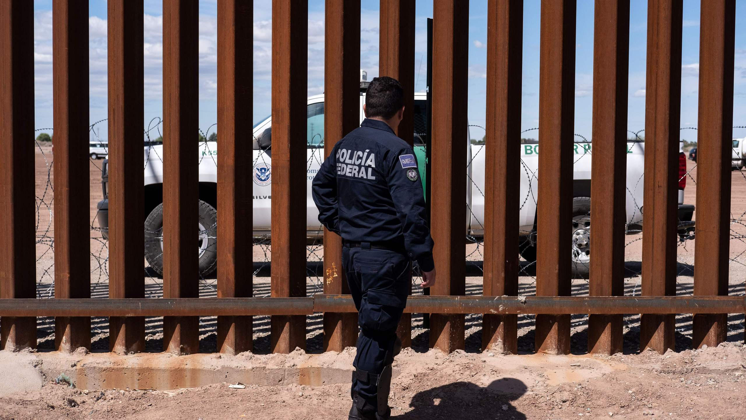 A Border patrol unit and a Mexican federal police guard stop near the U.S.-Mexico border fence in Calexico, California. (Credit: GUILLERMO ARIAS/AFP/Getty Images)