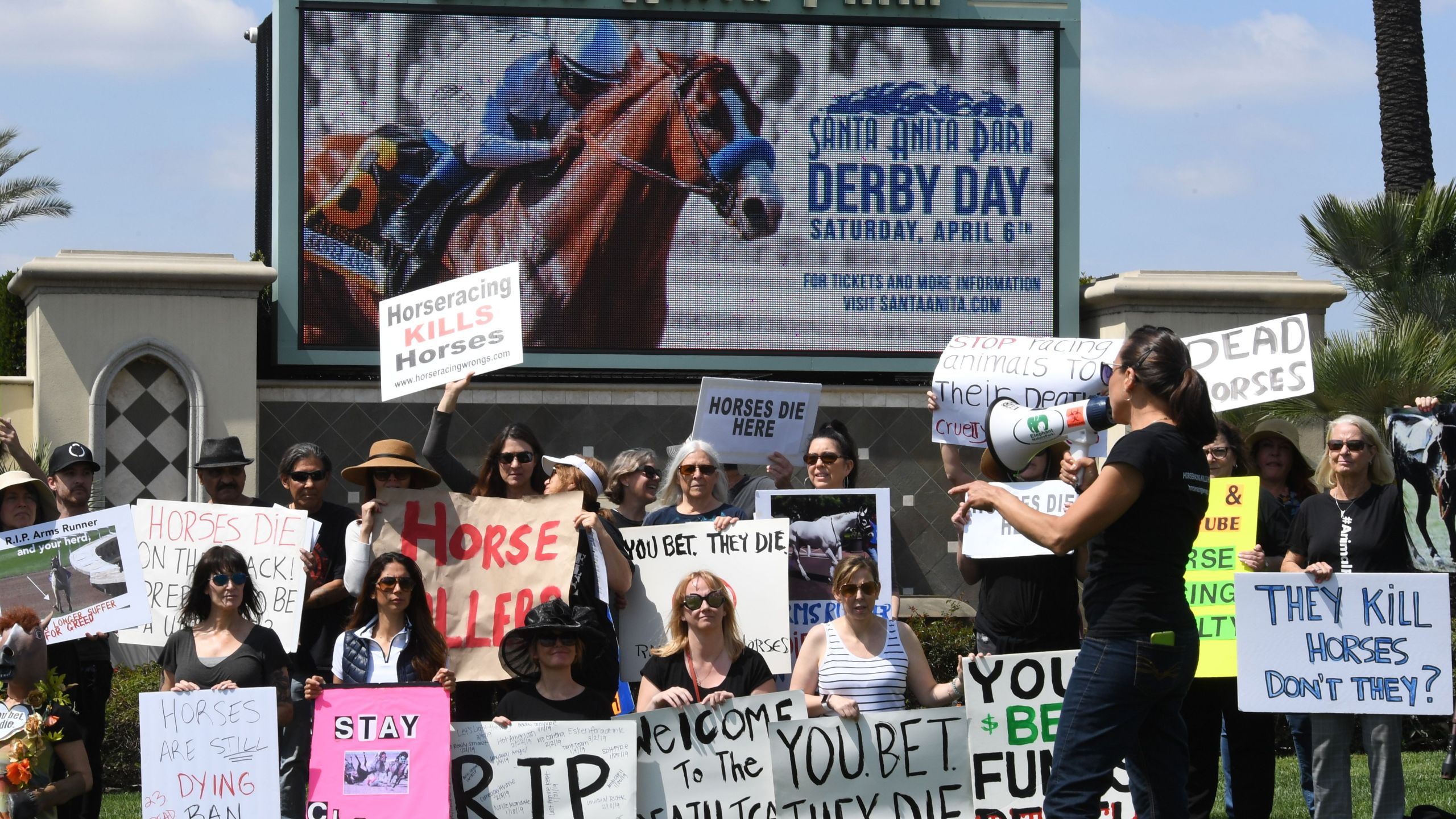 Animal-rights advocates protest beside the racetrack entrance gate after the deaths of 23 racehorses in the first three months of 2019 at the Santa Anita Park in Arcadia, April 6, 2019. (Credit: Mark Ralston / AFP / Getty Images)