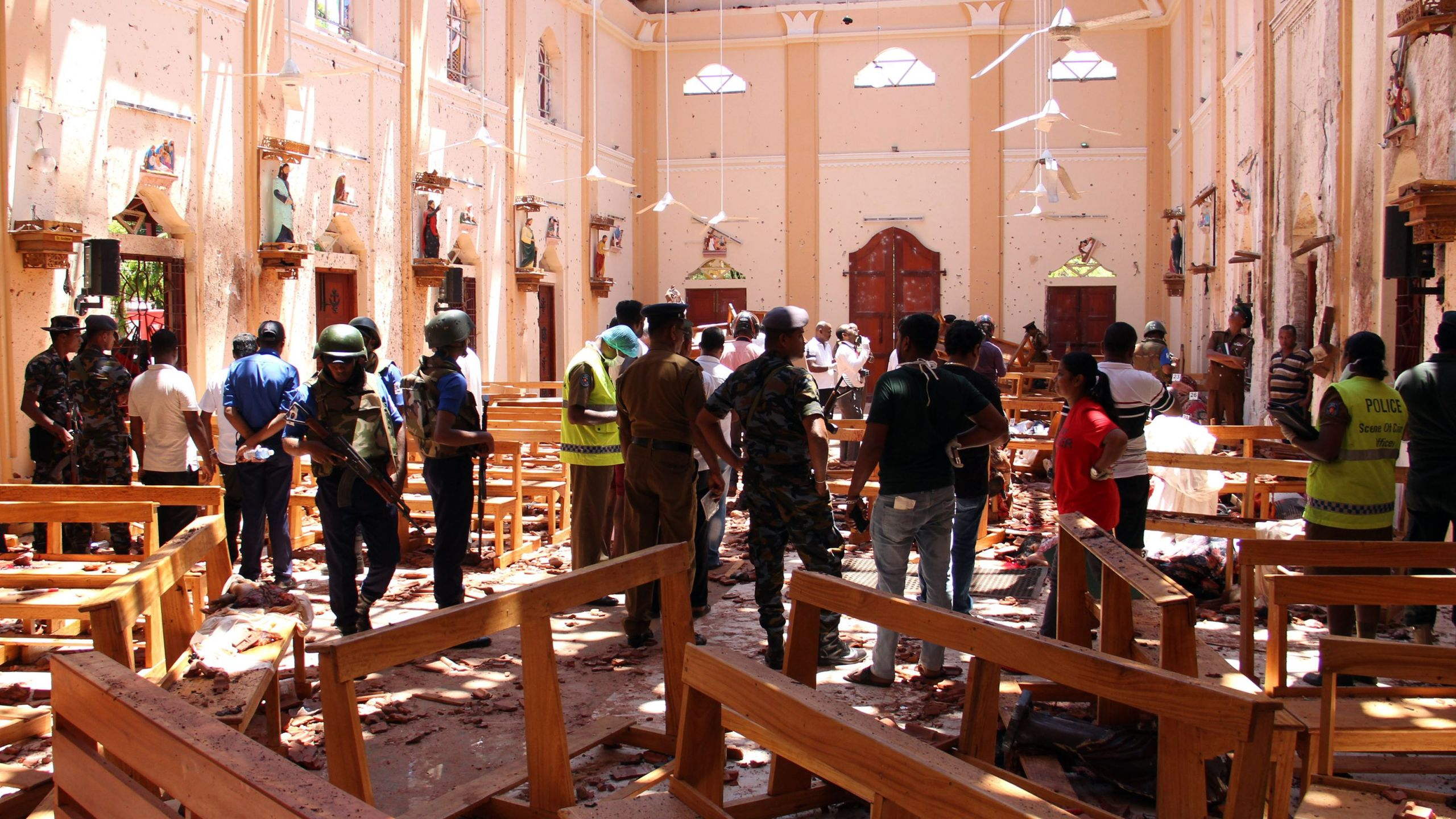 Sri Lankan security personnel walk through debris following an explosion in St. Sebastian's Church in Negombo, north of the capital Colombo, on April 21, 2019. (Credit: STR/AFP/Getty Images)