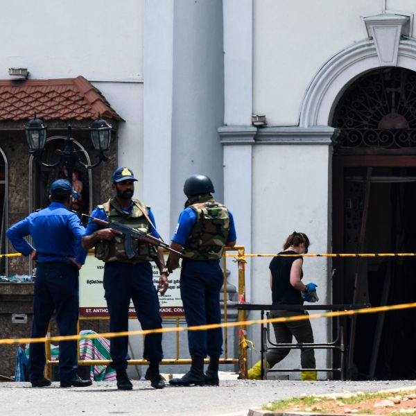 A foreign investigator (R) walks into St. Anthony's Shrine as soldiers stand guard in Colombo on April 25, 2019. (Credit: JEWEL SAMAD/AFP/Getty Images)