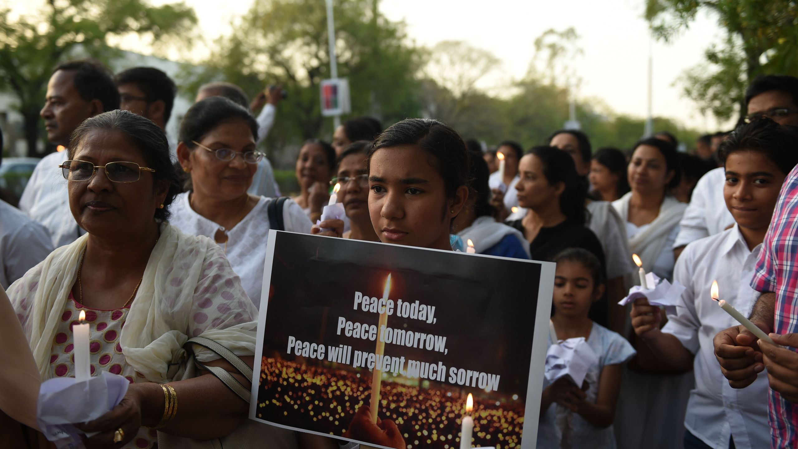 "Indian Christians hold placards and candles as they participate in a peace march to show solidarity with the Sri Lankan victims of the last week's serial bombings in Ahmedabad on April 28, 2019. Sri Lanka's churches remained shuttered on April 28, 2019, forcing Christians to say prayers of grief in private over the Easter suicide attacks that the country's Roman Catholic leader called ""an insult to humanity"". (Credit: SAM PANTHAKY/AFP/Getty Images)"