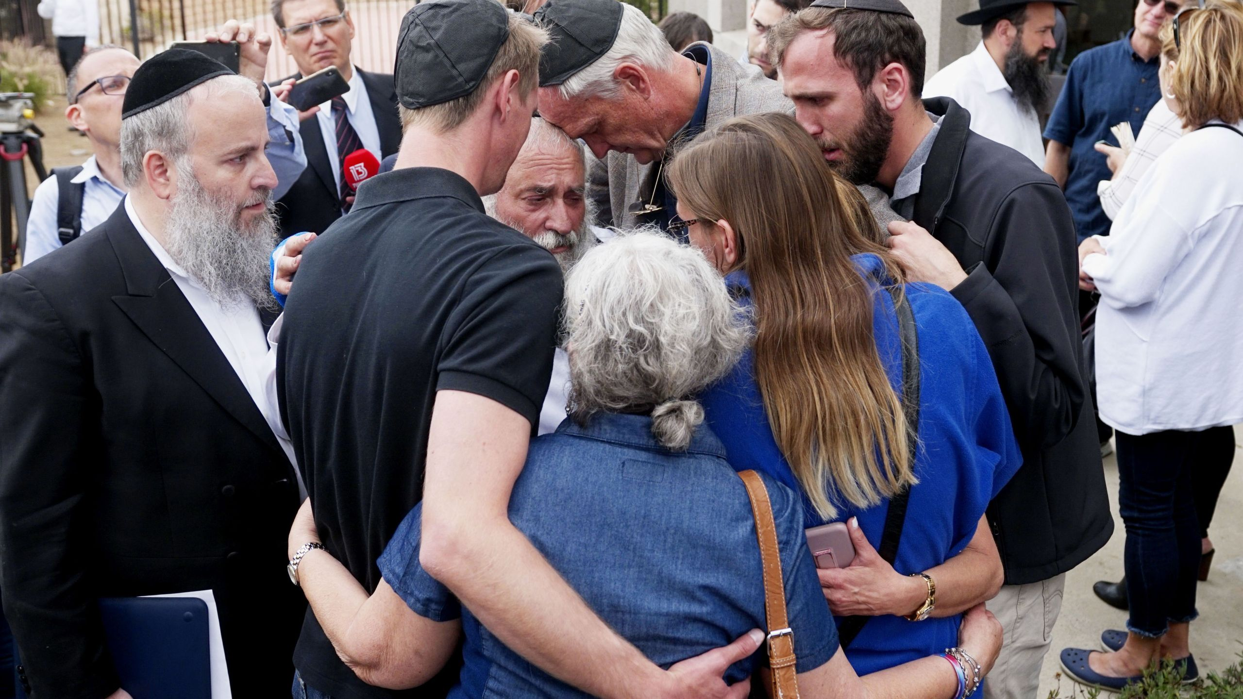 Executive Director Rabbi Yisroel Goldstein (center), who was shot in the hands, hugs his congregants after a press conference outside the Chabad of Poway Synagogue on April 28, 2019. (Credit: SANDY HUFFAKER/AFP/Getty Images)