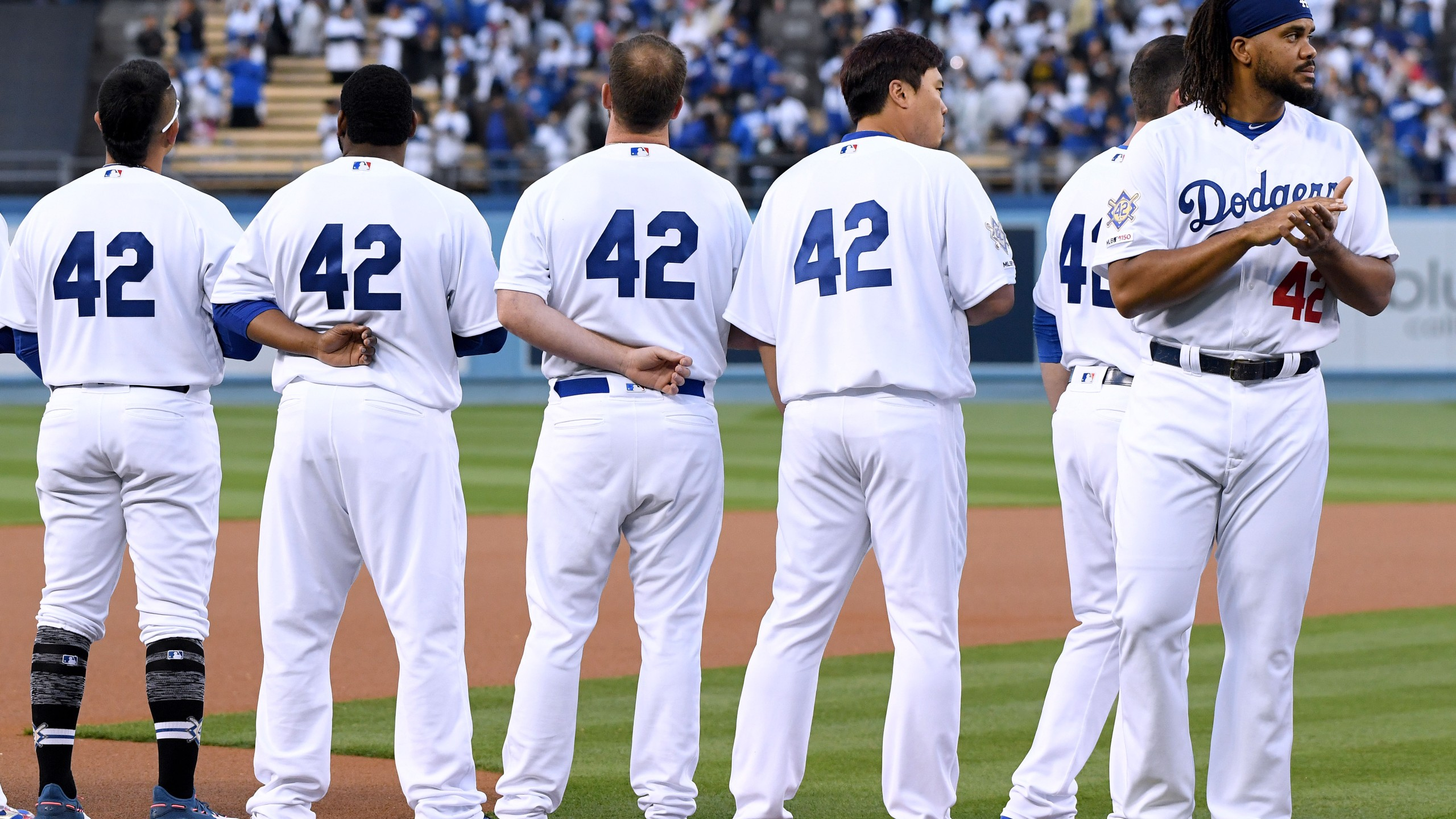 Kenley Jansen, far right, and other members of the Los Angeles Dodgers line up for the National Anthem before a game against the Cincinnati Reds on Jackie Robinson Day at Dodger Stadium on April 15, 2019. (Credit: Harry How / Getty Images)