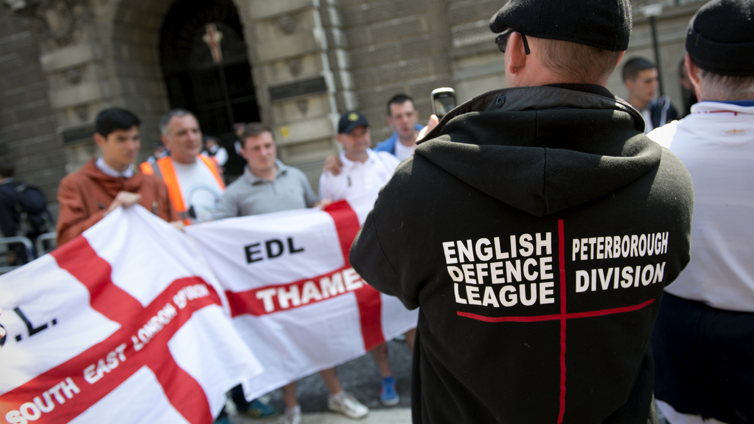 Members of the English Defence League (EDL) pose for a photograph during a rally outside the Old Bailey, in London, on June 6, 2013. (Credit: ADRIAN DENNIS/AFP/Getty Images)