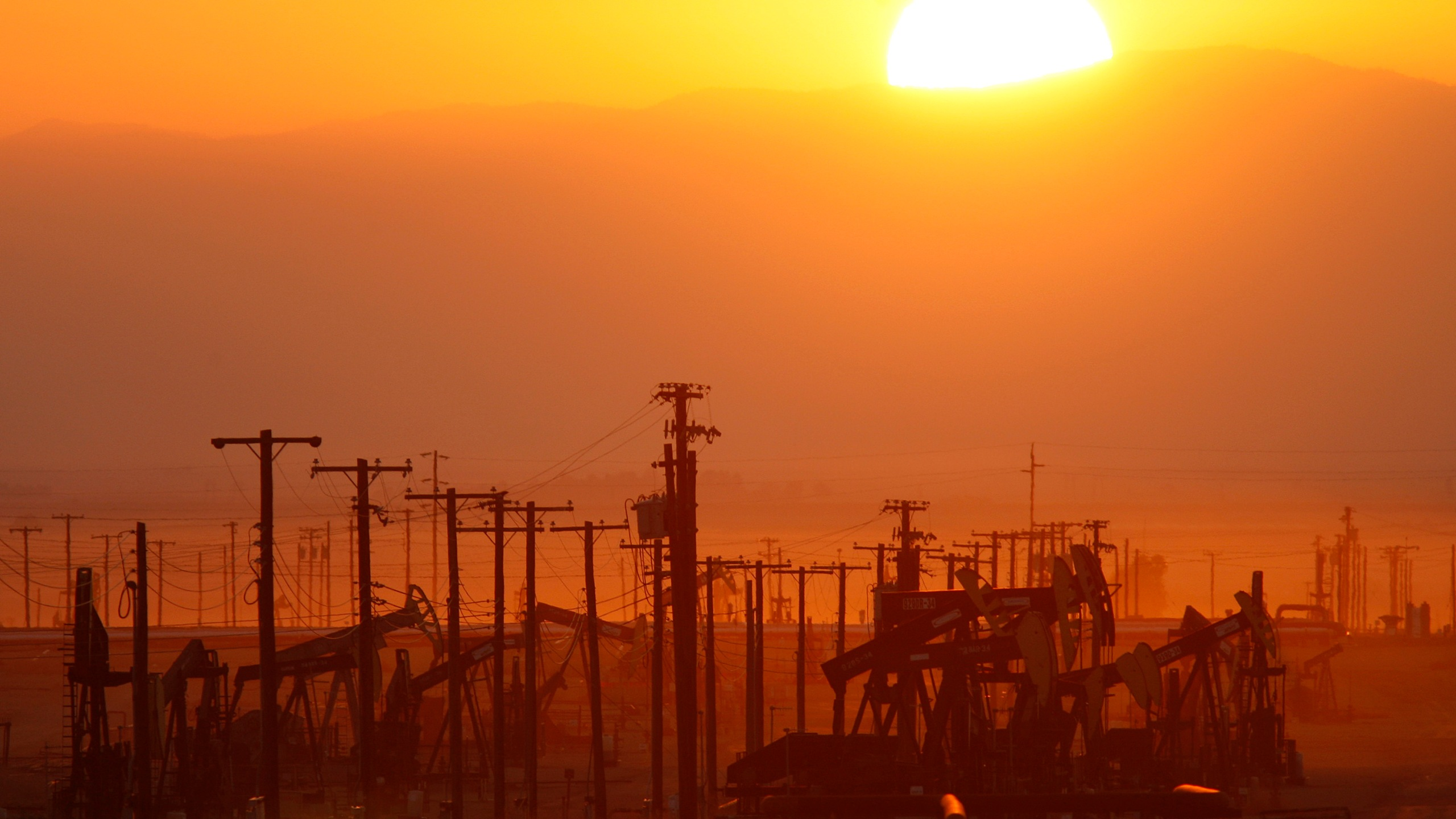 The sun rises over an oil field at the Monterey Shale formation on March 24, 2014, near Lost Hills, California. (Credit: David McNew/Getty Images)