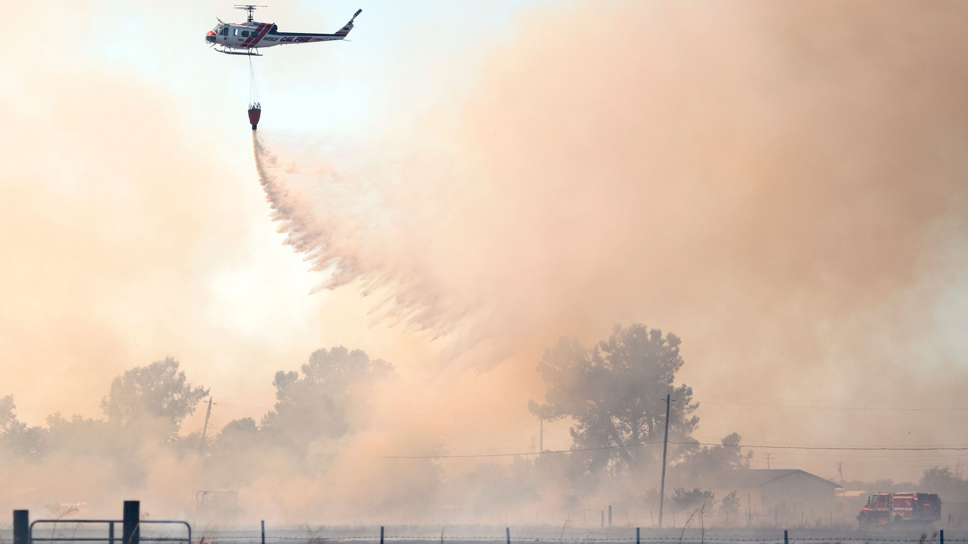 A helicopter drops water on a fire that broke out in Butte County, California on July 10, 2017. (Credit: Josh Edelson/AFP/Getty Images)