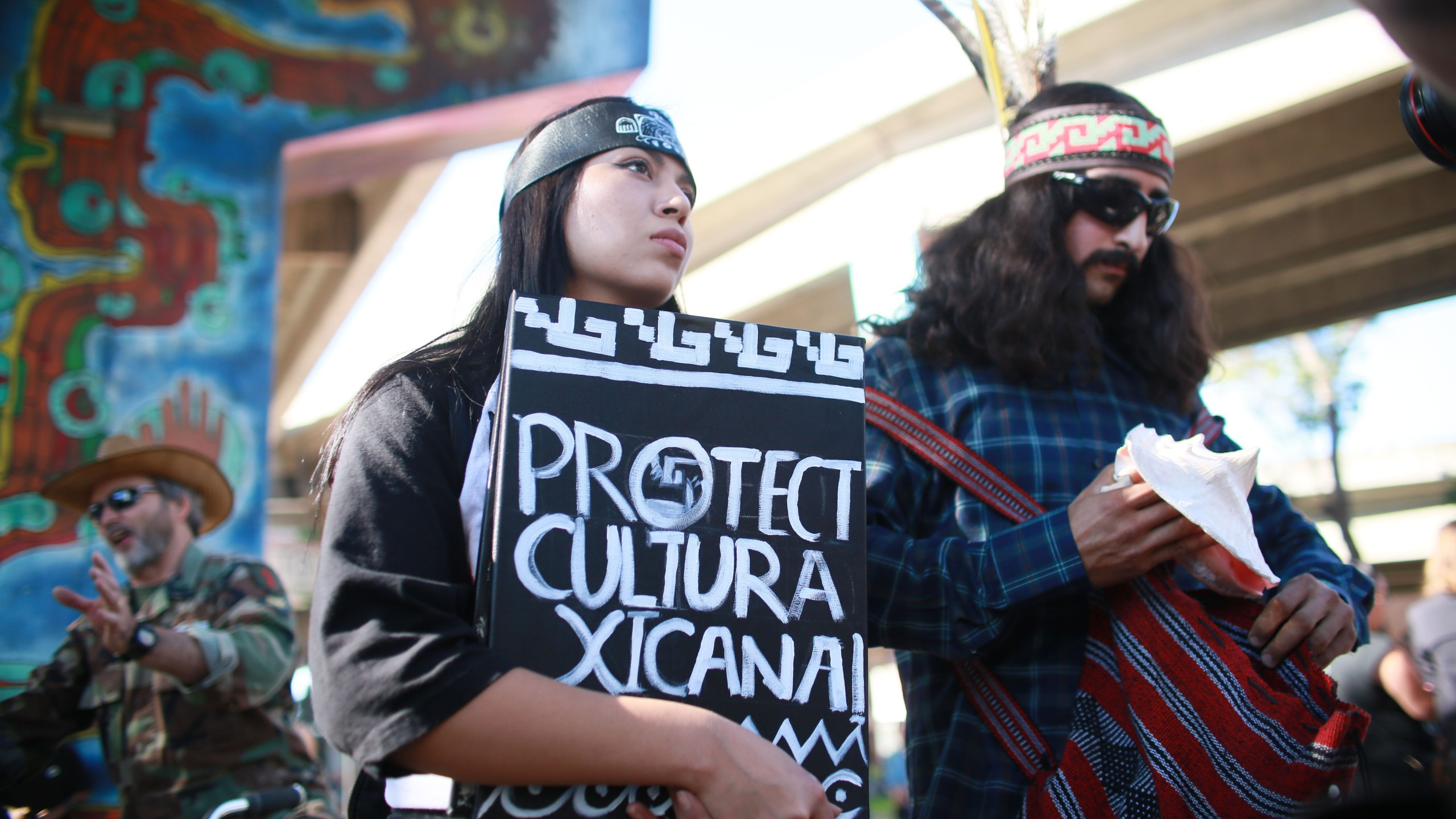 """A Xicana rights protester stands across from a pro-Trump """"Patriot Picnic"""" rally at Chicano Park on Feb. 3, 2018, in San Diego. (Credit: SANDY HUFFAKER/AFP/Getty Images)"""
