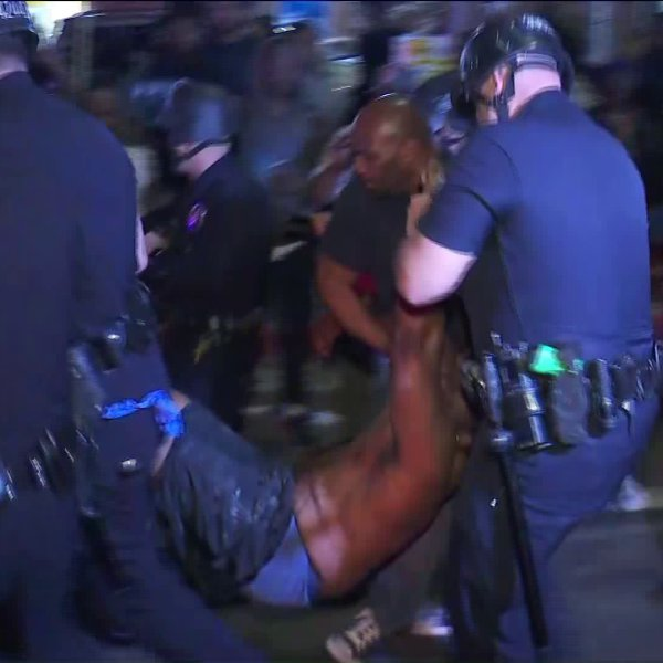 Police move a man injured at a vigil for slain rapper Nipsey Hussle in Hyde Park on Monday. (Credit: KTLA)
