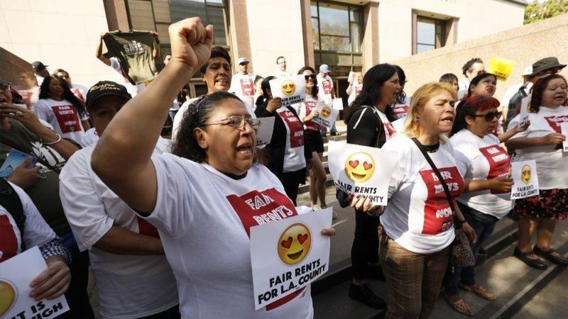 Maria Leon, left, from East Los Angeles, joins a crowd on the steps of the Los Angeles County Hall of Administration on April 9, 2019, to urge supervisors to extend a rent increase cap through 2019. (Credit: Al Seib / Los Angeles Times)