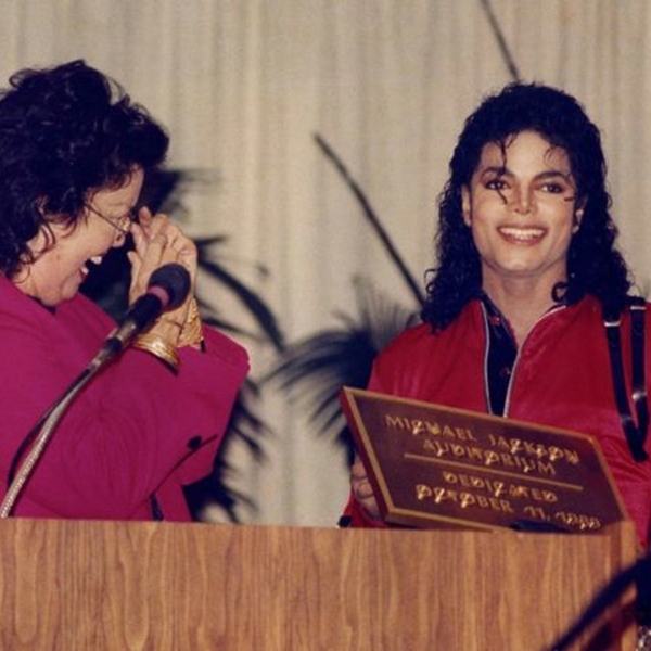 An L.A. school that honored Michael Jackson may remove his name from its auditorium. In this photo from 1989, Jackson reunites with sixth-grade teacher Laura Gerson during the naming ceremony at Gardner Elementary. (Credit: Los Angeles Times)