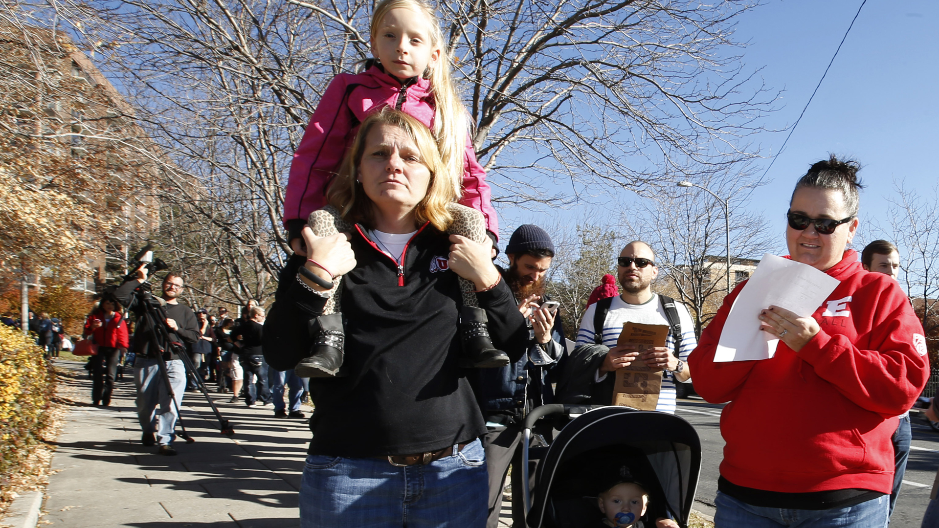 While her wife Debbie (left) and kids Chole and Cason stand in line, Trisha Allen-Gibby fills out papers for her and her family to resign from the Church of Jesus Christ of Latter-Day Saints in response to a recent change in church policy towards married LGBT same-sex couples and their children on Nov. 14, 2015, in Salt Lake City, Utah. A little over a week earlier, the Mormon church made a change in their official handbook of instructions requiring a disciplinary council and possible excommunication for same-sex couples and banning the blessing and baptism of their children into the church. (Credit: George Frey/Getty Images)