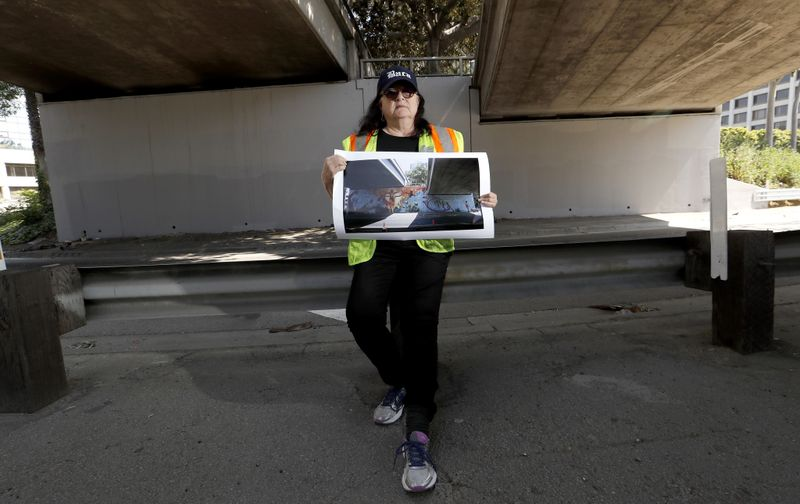Artist Judy Baca stands in front of a wall along the 110 Freeway in downtown Los Angeles where her mural was covered by gray paint in March 2019. (Credit: Luis Sinco / Los Angeles Times)