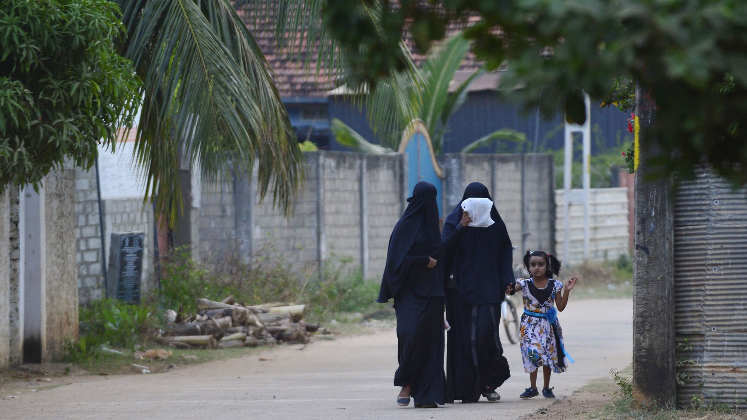 Sri Lankan Muslim women walk with a girl along a road in Kattankudy, Sri Lanka in an undated image. Credit: Lakruwan Wanniarchchi/Getty Images via CNN)