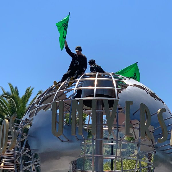 Two protesters sit atop the globe at Universal Studios Hollywood on April 22, 2019. (Credit: @Secretkat3 via Twitter)