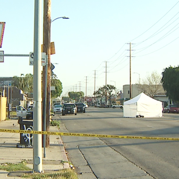 A victim's body is covered by a tent as police respond to investigate a fatal hit-and-run crash in South Los Angeles on April 9, 2019. (Credit: KTLA)