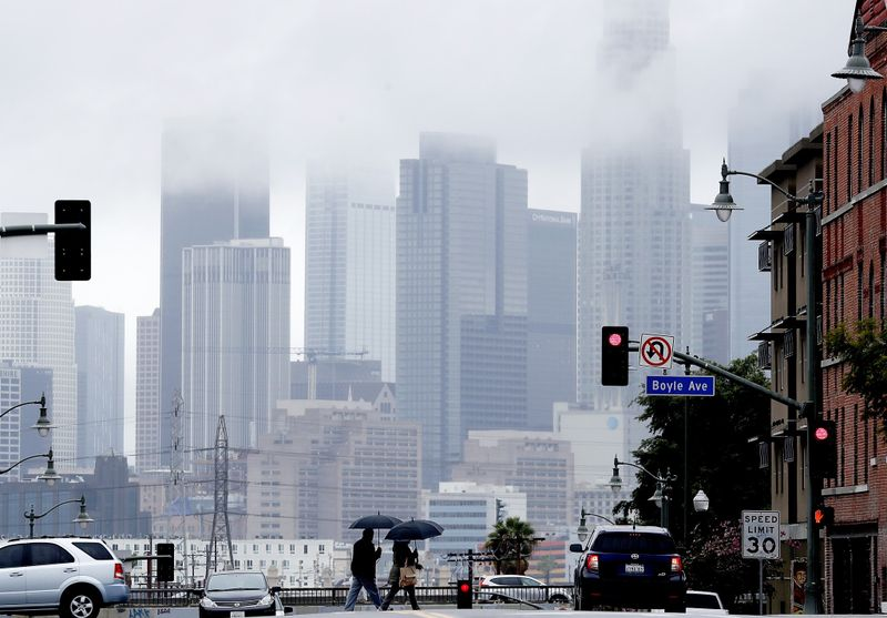 Pedestrians cross First Street in Boyle Heights as rain clouds partially obscure the downtown L.A. skyline during a storm in March 2019. (Credit: Luis Sinco / Los Angeles Times)