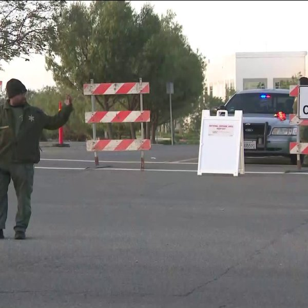 A man directs traffic on May 17, 2019, near March Air Reserve Base, in the area where an F-16 fighter jet crashed the previous day. (Credit: KTLA)