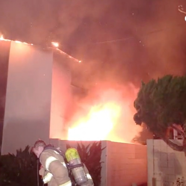 A fire burns at an apartment building in Anaheim as firefighters work to put out the flames May 26, 2019. (Credit: OC Hawk)