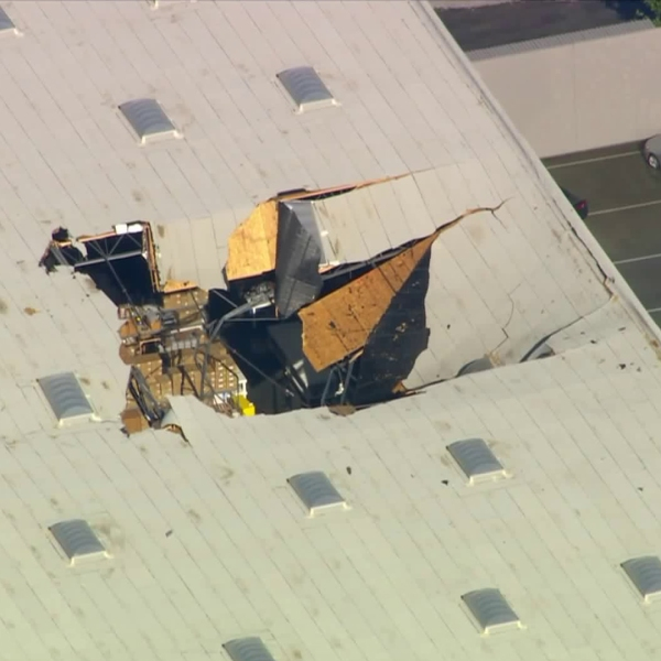 A large hole is visible in the roof of a building after an F-16 pilot ejected just before the aircraft crashed near March Air Reserve Base in Riverside County on May 16, 2019. (Credit: KTLA)