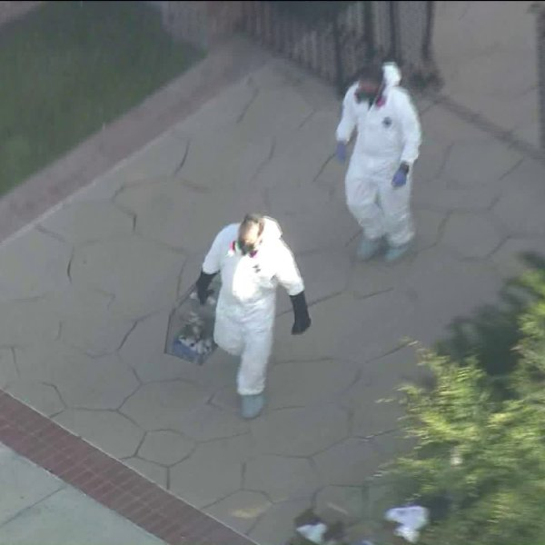 Officials donnned hazmat suits as they removed nearly 100 dogs from a home in the City of Orange on May 30, 2019. (Credit: KTLA)