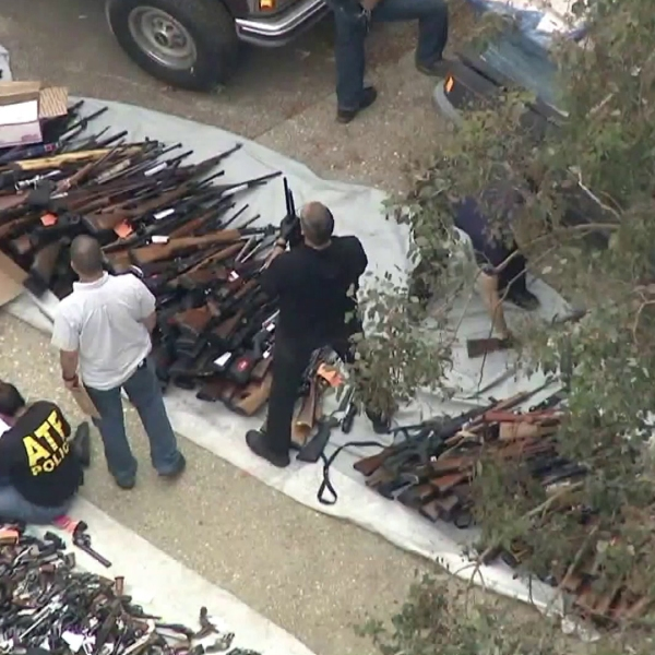 ATF agents and LAPD officers examine a massive weapons cache found at a Bel-Air home on May 8, 2019. (Credit: KTLA)