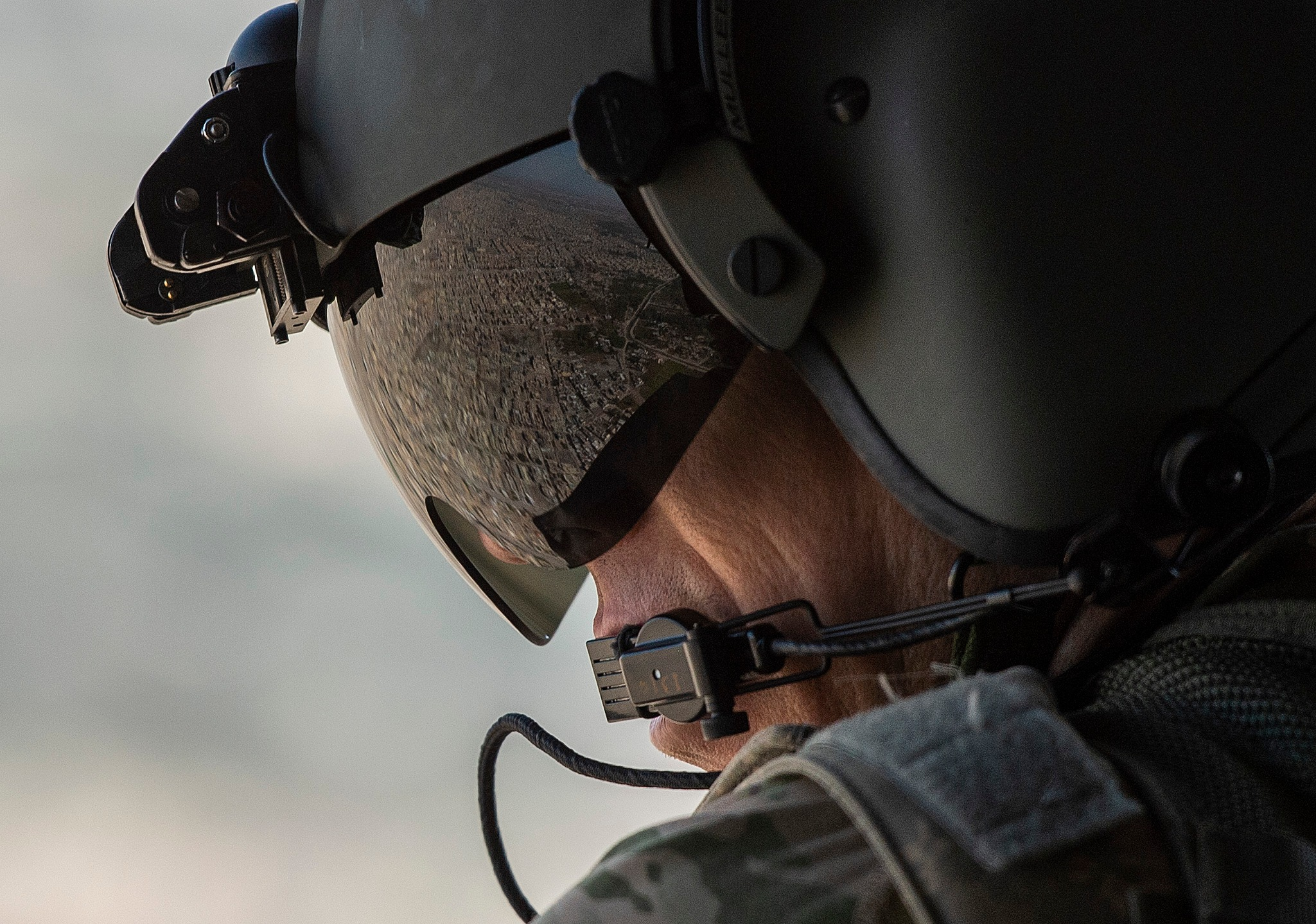 A partial view of the Iraqi capital Baghdad is reflected in the visor of a U.S. Army helicopter crew member as he looks out of a Chinook flying from the U.S. Embassy to Baghdad International Airport on Jan. 9, 2019. (Credit: Andrew Caballero-Reynolds / AFP / Getty Images)