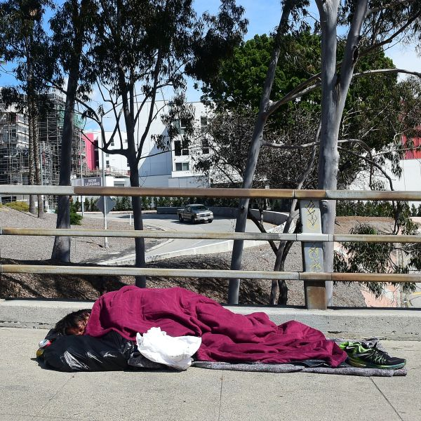 A homeless man sleeps on a sidewalk in Los Angeles on March 10, 2019. (Credit: Frederic J. Brown / AFP / Getty Images)