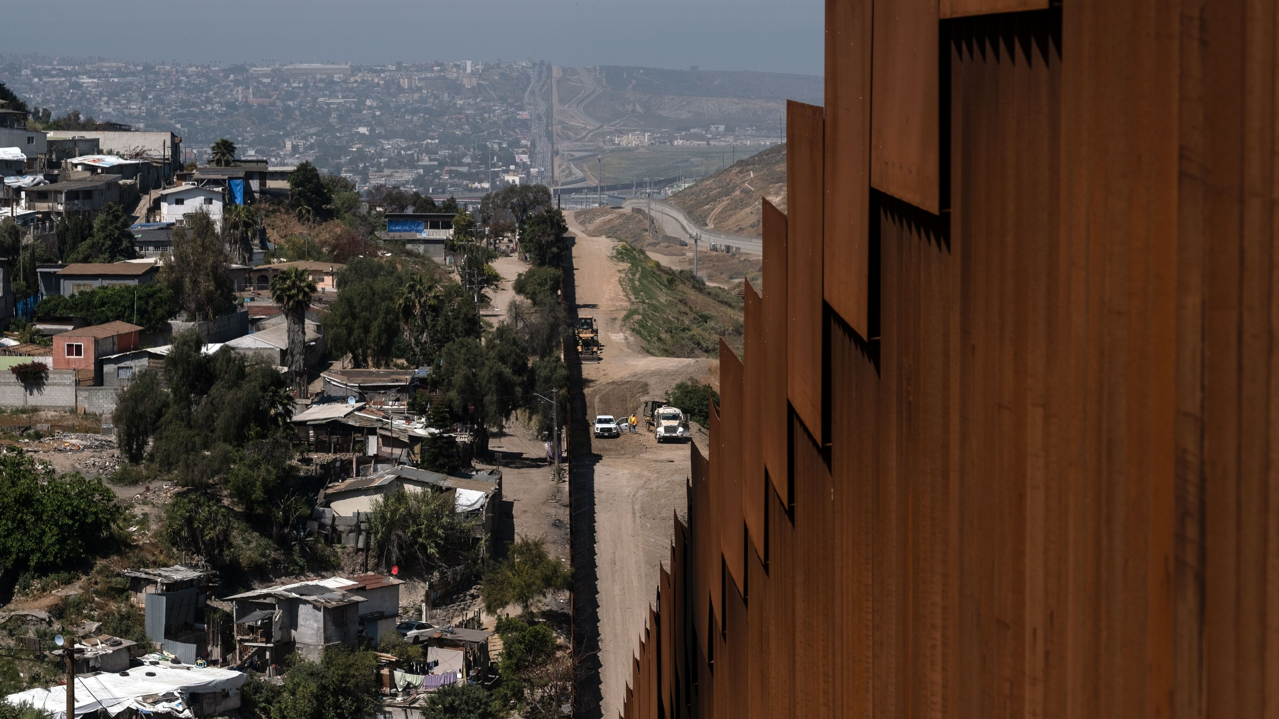 A construction crew (right) works on the US side of the US-Mexico border fence as seen from Tijuana, in Baja California state, Mexico, on April 24, 2019. (Credit: GUILLERMO ARIAS/AFP/Getty Images)