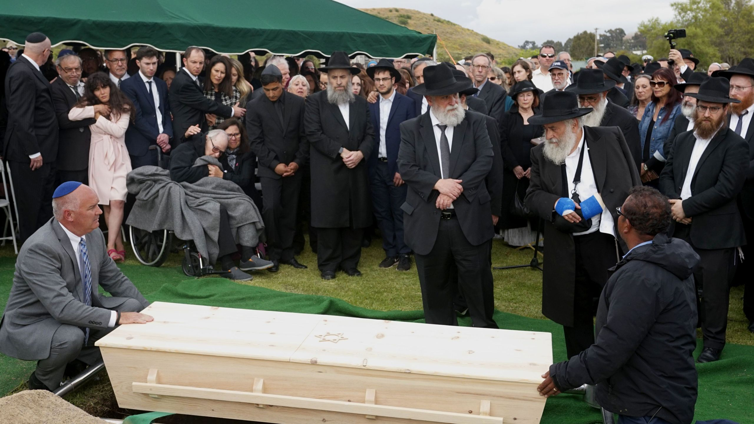 Mourners look over a coffin during the burial service for Lori Gilbert Kaye, who was killed in the Chabad of Poway Synagogue shooting, at El Camino cemetery in San Diego on April 29, 2019. (Credit: SANDY HUFFAKER/AFP/Getty Images)