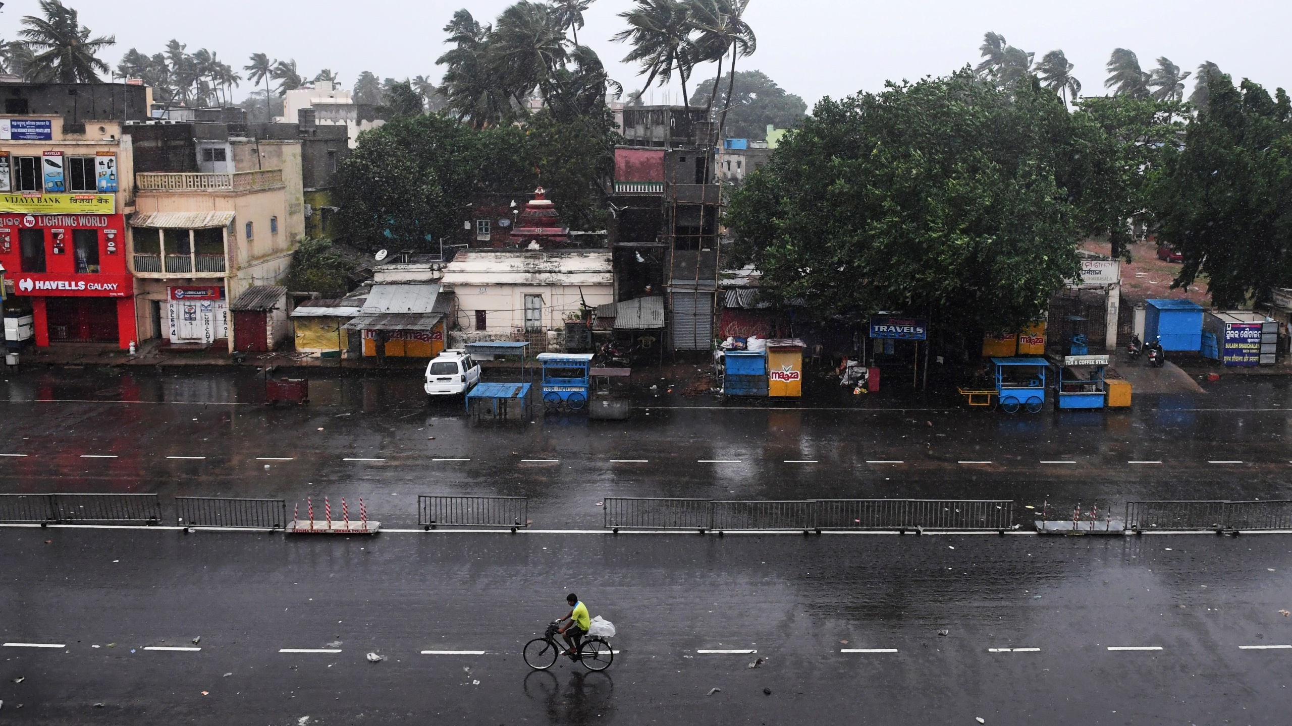 A lone Indian commuter (C) cycles down nearly deserted road in Puri in the eastern Indian state of Odisha early on May 3, 2019, as Cyclone Fani approaches the Indian coastline. (Credit: DIBYANGSHU SARKAR/AFP/Getty Images)