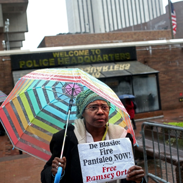 An activist who goes by the name Sista Shirley, 62, from Staten Island, holds up a sign as a line of people awaits entry to the trial of Officer Daniel Pantaleo at One Police Plaza on May 13, 2019 in New York City. (Credit: Yana Paskova/Getty Images)