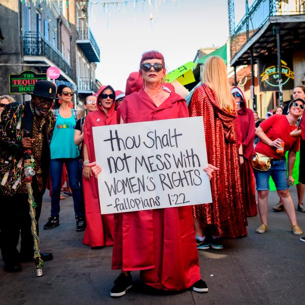 """""""The Handmaid's Tale""""-themed protesters march down Bourbon Street in the French Quarter of New Orleans, Louisiana, on May 25, 2019, to protest the proposed heartbeat bill that will ban abortion after six weeks in that state scheduled. (Credit: Emily Kask / AFP / Getty Images)"""