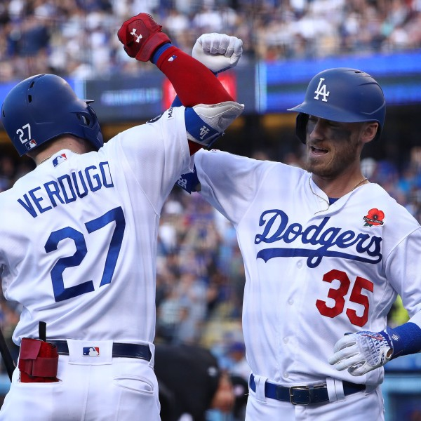 Cody Bellinger, No. 35 of the Los Angeles Dodgers, celebrates with teammate Alex Verdugo, No. 27, after Bellinger hit a solo home run in the third inning of the game against the New York Mets at Dodger Stadium on May 27, 2019. (Credit: Victor Decolongon / Getty Images)