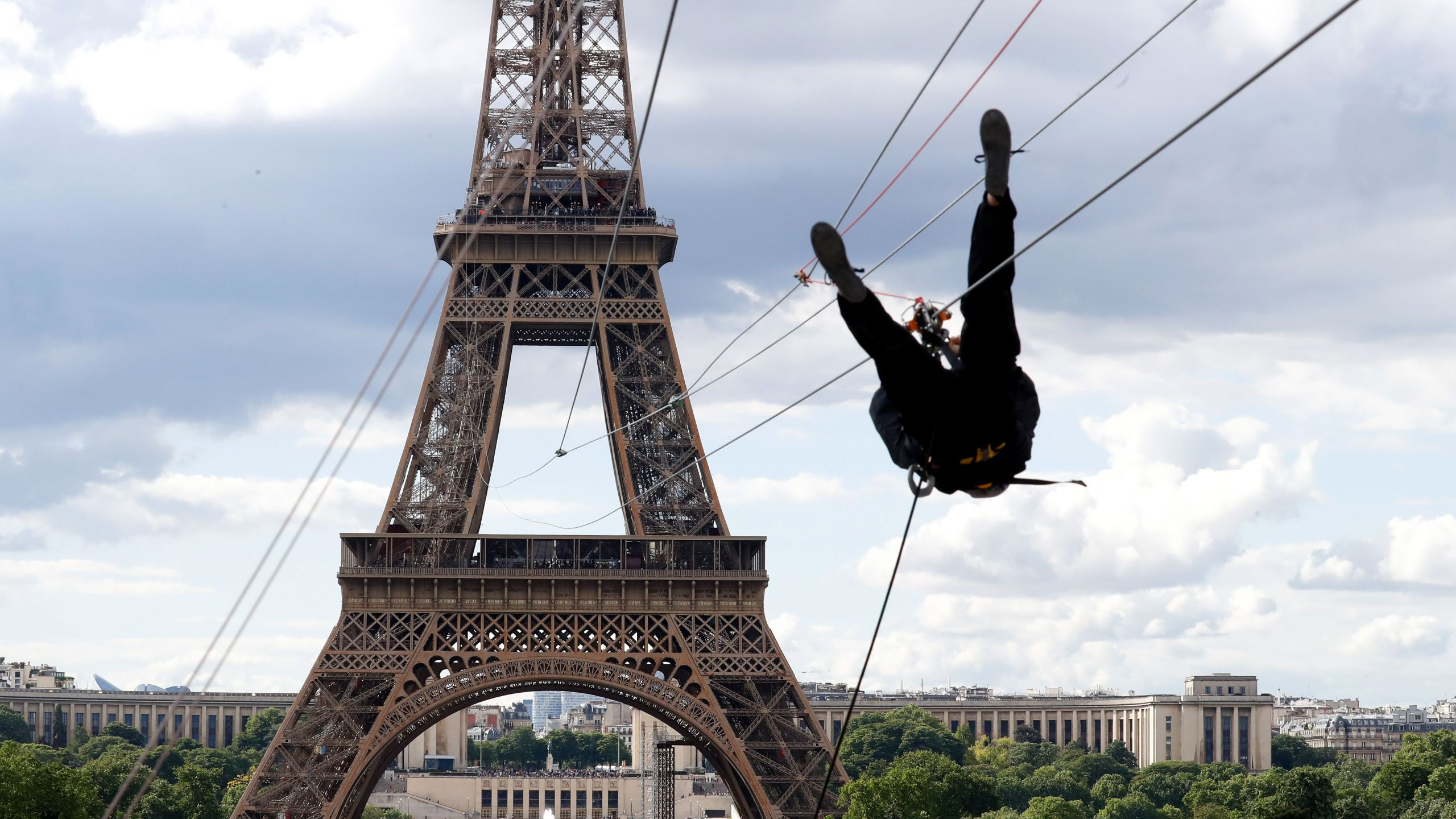 A person rides on a zip-line descending from the second floor of the Eiffel Tower on May 28, 2019 in Paris. (Credit: FRANCOIS GUILLOT/AFP/Getty Images)