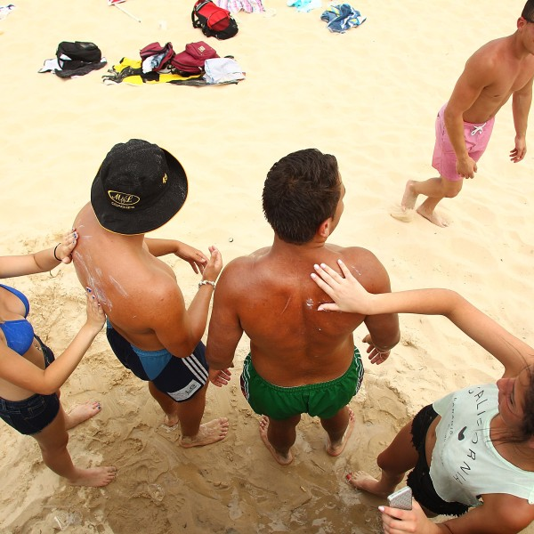 Beach-goers apply sunscreen to each other at Bondi Beach on January 8, 2013 in Sydney, Australia. (Credit: Marianna Massey/Getty Images)