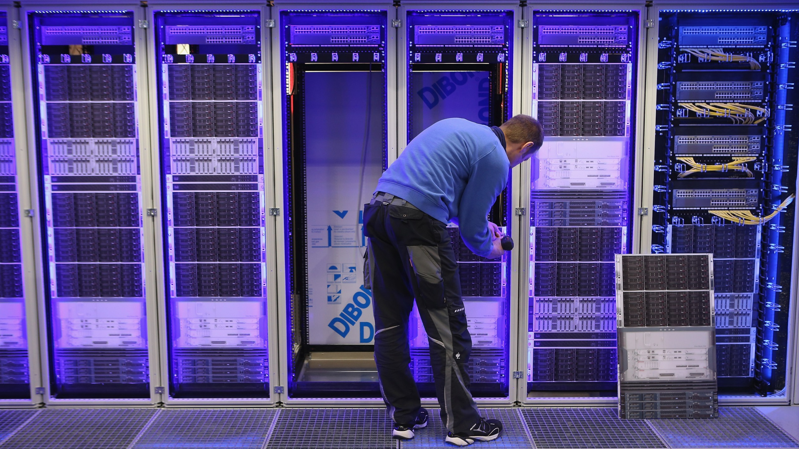 A worker assembles a data center module container at the Rittal stand at the 2013 CeBIT technology trade fair in Hanover, Germany, on March 4, 2013. (Credit: Sean Gallup / Getty Images)