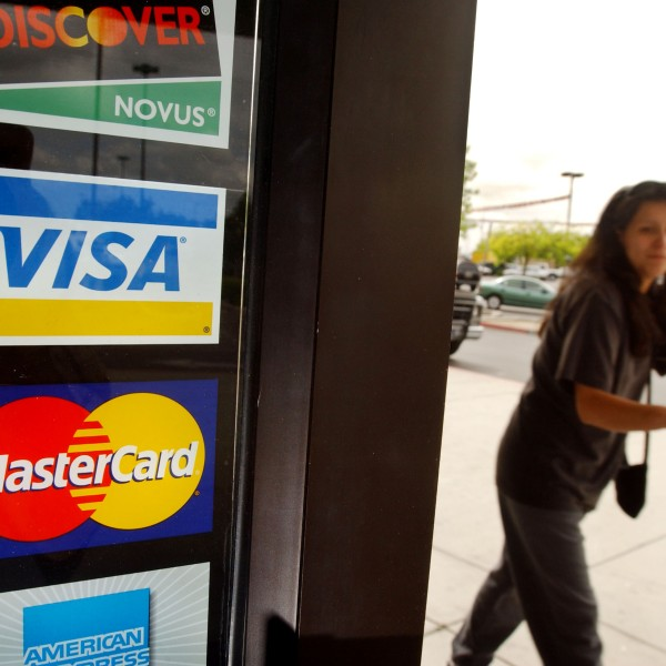 A shopper passes a shop door advertising acceptance of purchases with Master Card, Visa, and other credit cards in Bakersfield on April 29, 2003. (Credit: David McNew/Getty Images)