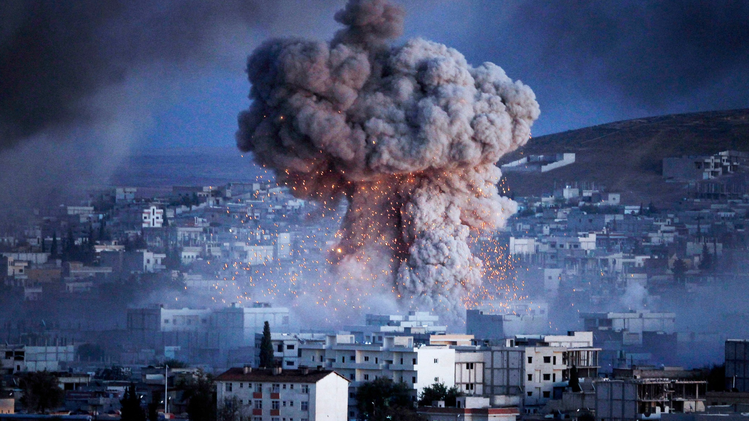 An explosion rocks Syrian city of Kobani during a reported suicide car bomb attack by the militants of Islamic State (ISIS) group on a People's Protection Unit (YPG) position in the city center of Kobani, as seen from the outskirts of Suruc, on the Turkey-Syria border, October 20, 2014 in Sanliurfa province, Turkey. (Credit: Gokhan Sahin/Getty Images)